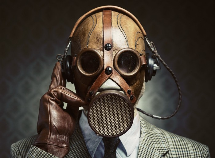 Man in suit, wearing a gas mask.