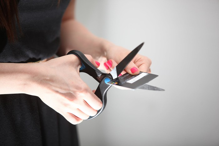 Woman cutting credit card in half.