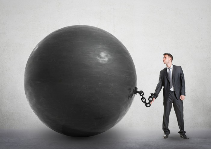 Man in suit chained to giant ball, like a prisoner.