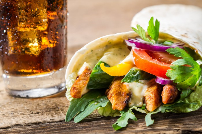 Image of a chicken wrap and soft beverage.