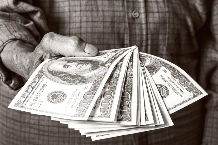 A senior holding a pile of cash.