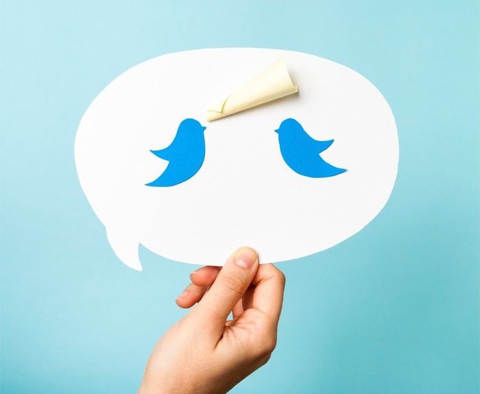 A hand holding a speech bubble with two Twitter bluebirds.