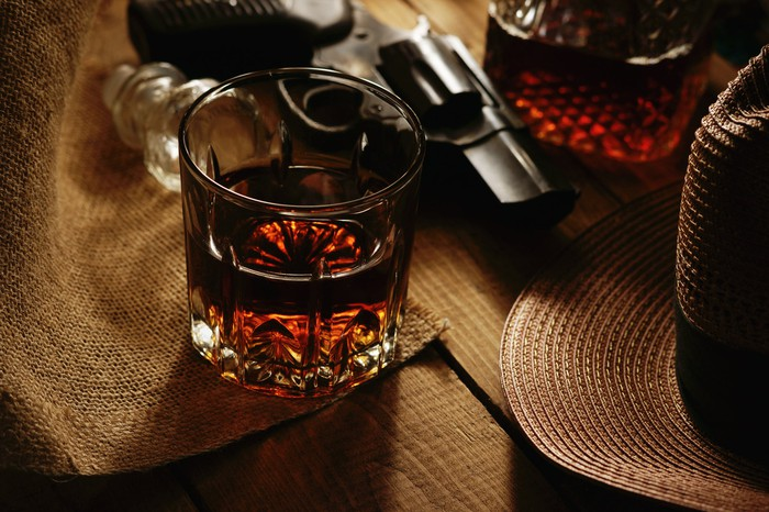 A glass of whiskey and a revolver.