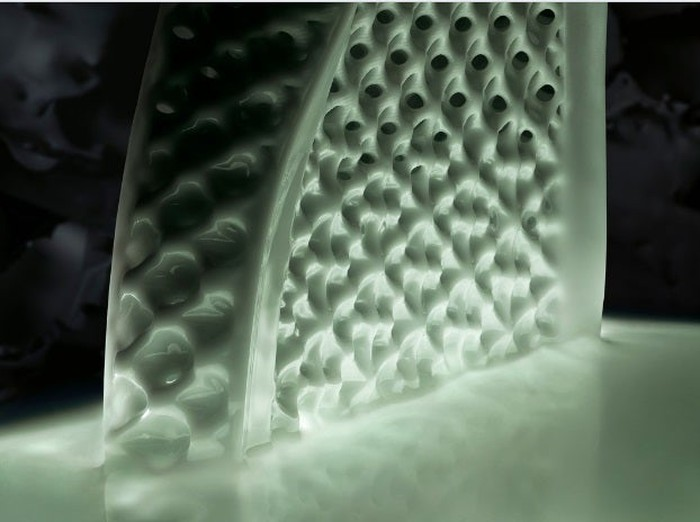 Close-up of a midsole rising from a pool of liquid resin in a Carbon 3D printer.