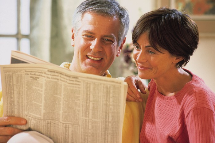 A baby boomer couple looking for value stocks in a financial newspaper.