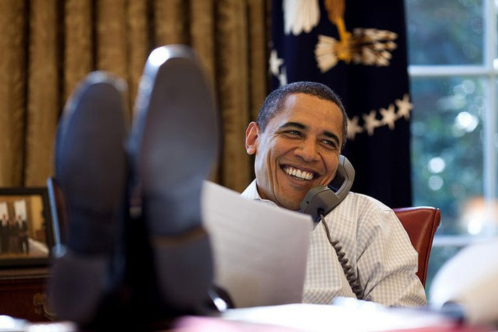 Former President Barack Obama smiling with his feet up on his desk in the Oval Office.