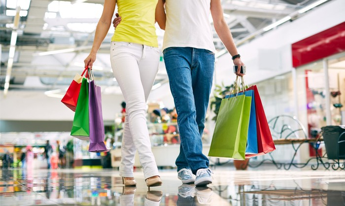 A male and female shopper holding shopping bags.