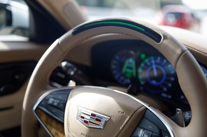 A close up of the Cadillac's steering wheel, showing a light built in. The light is green in the photo.