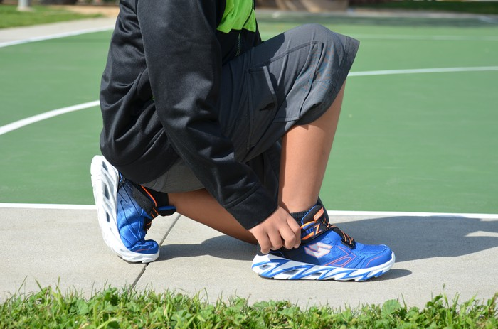 A person adjusting Skechers shoes at a basketball court.