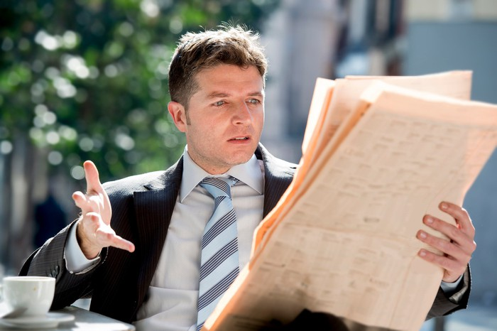 A businessman is upset while reading a newspaper and having coffee