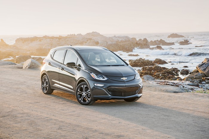 A black Chevrolet Bolt EV before a rocky waterfront.