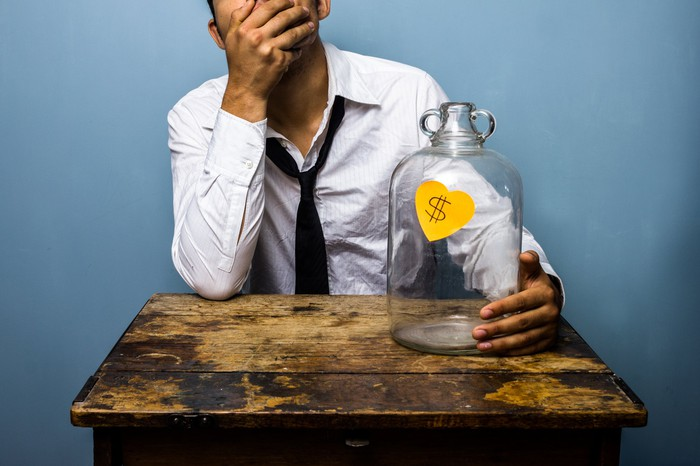 A man with his hand in his face, grasping an empty savings jar.