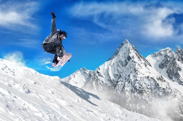 Snowboarder jumping down a mountain