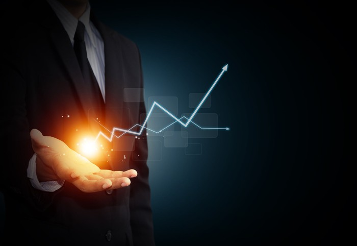A man in a suit holds his palm out; above it hovers a ball of light, from which emanates a rising arrow as in a stock chart.