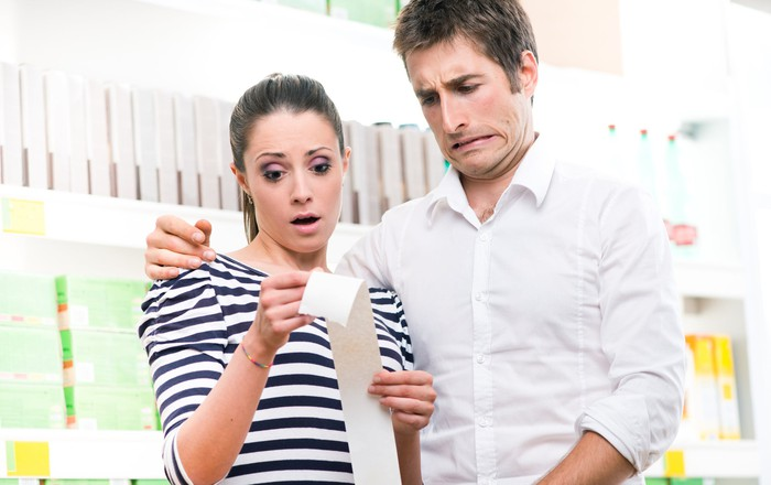 A young couple horrified by the prices on their receipt, implying high inflation levels.