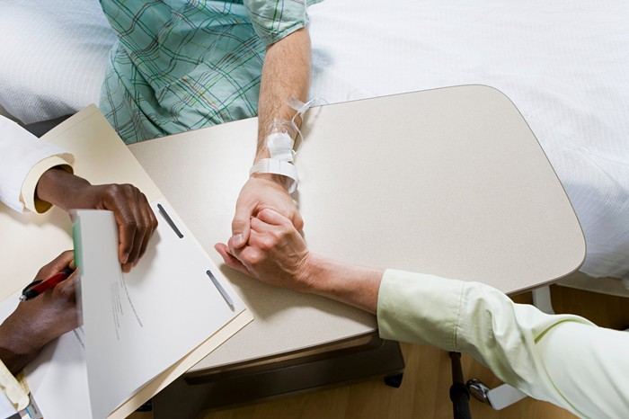 Doctor holding a patient's hand.