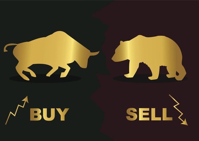"""The words """"buy"""" and """"sell"""" under a bull fighting a bear"""