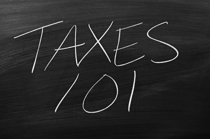 "The words ""taxes 101"" written on a blackboard."