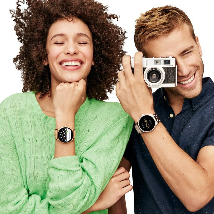 A man and a woman posing with a camera and wearing Fossil watches.