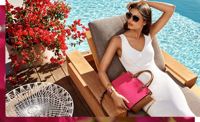 A woman in a white dress sits next to a pool with a pink Michael Kors handbag.