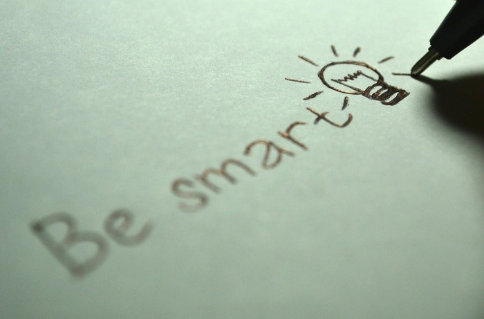 "A person writing ""Be Smart"" on a piece of paper."
