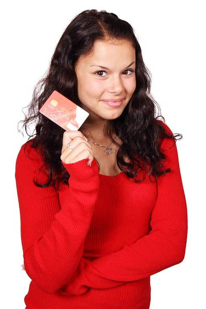A young adult holding a balance transfer card.
