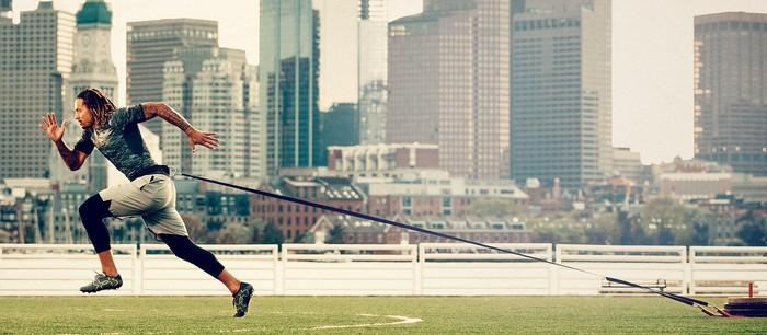 An athlete pulls a weight behind him attached to a cord while he runs across turf in Under Armour gear.