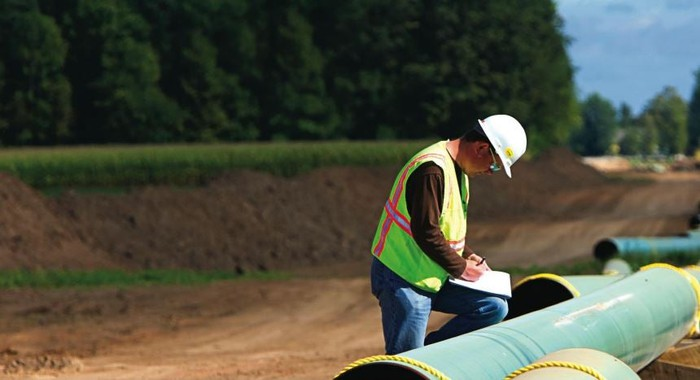 Pipeline worker installing pipe.