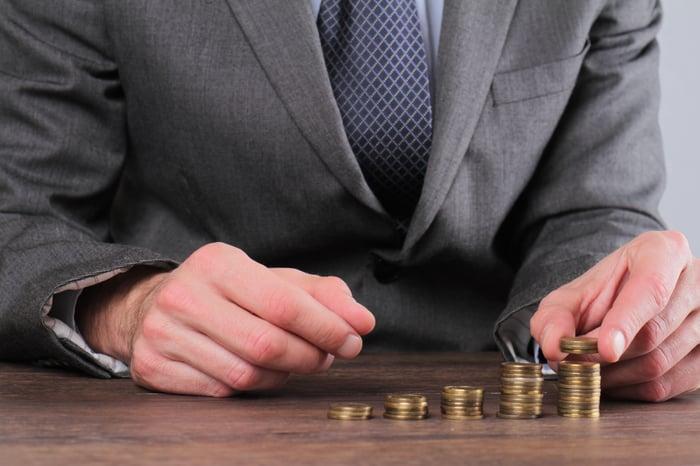 Businessman illustrating compound returns with stacks of change.