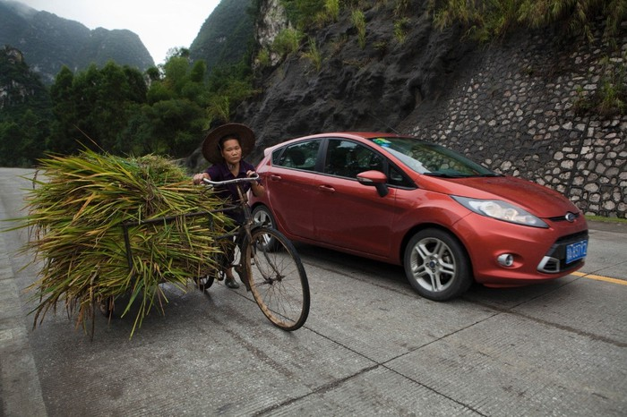 Ford's Fiesta on a mountain-lined street in China, driving alongside a cyclist
