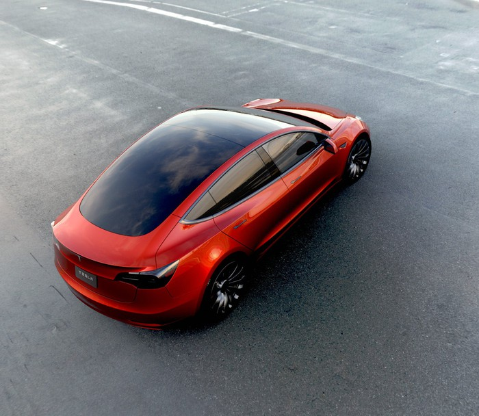 A red Tesla Model 3 sedan viewed from above.