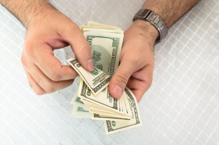 Close-up of a man's hands counting dollar notes