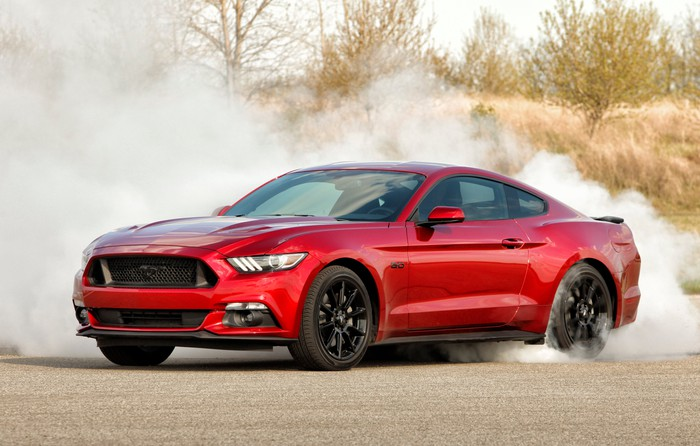 A red Ford Mustang GT spinning its rear tires