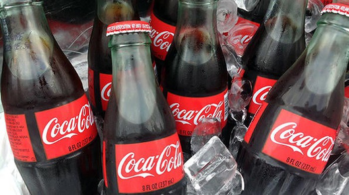 Bottles of Coca-Cola chill in a bucket of ice.