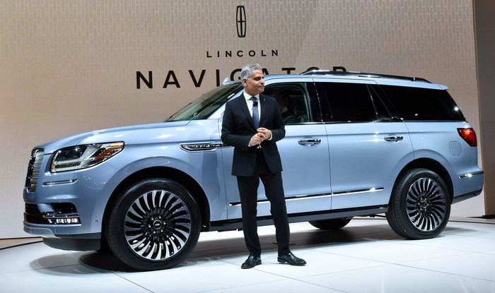 Galhotra stands in front of a light-blue Lincoln Navigator SUV.