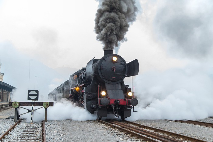 A locomotive chugging down the tracks, with steam pouring out.