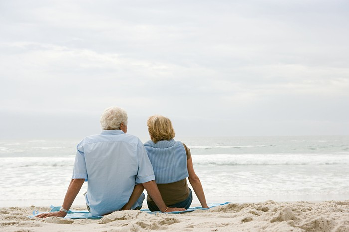 An older couple sit together on the beach.