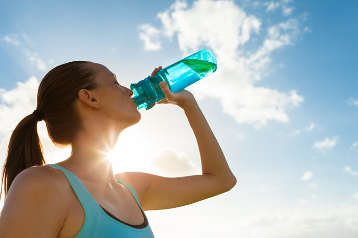 A woman in exercise clothing drinks from her water bottle.