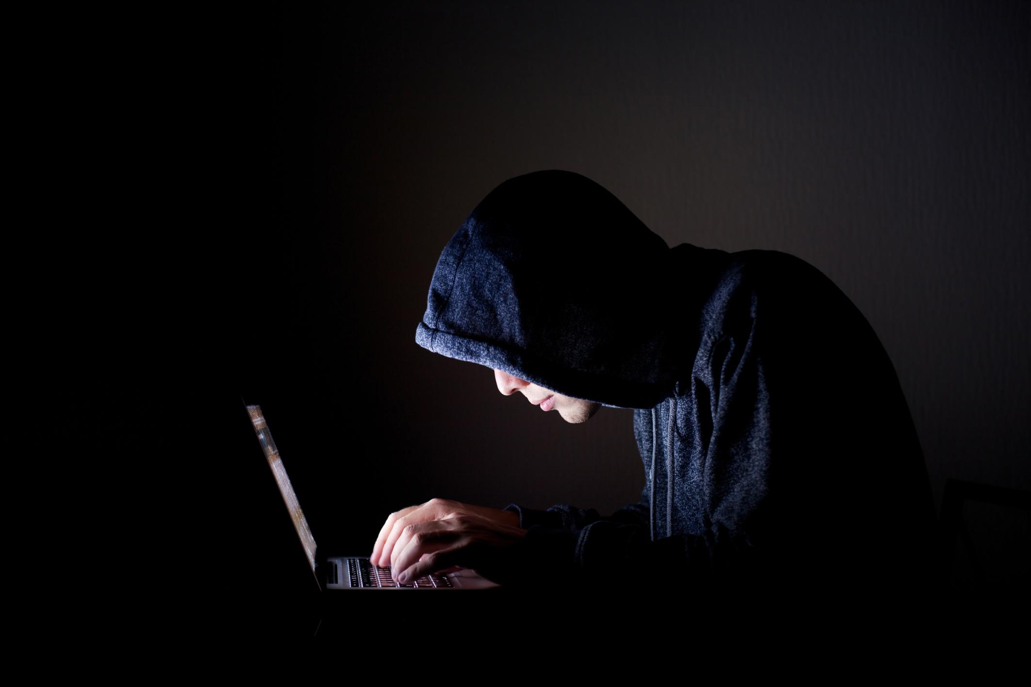 Man in dark hoodie leaning over laptop computer
