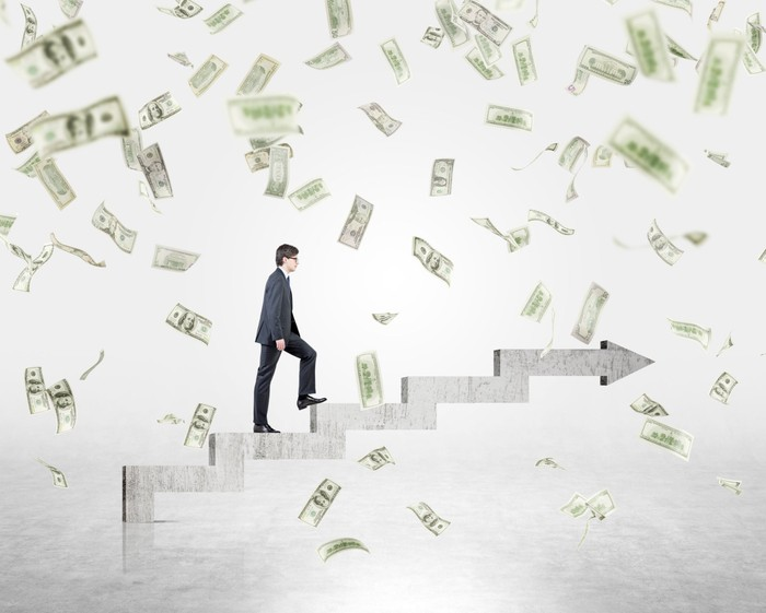 A businessman walking up steps with money falling all around him, indicative of management taking steps forward to generate more profits for a company.