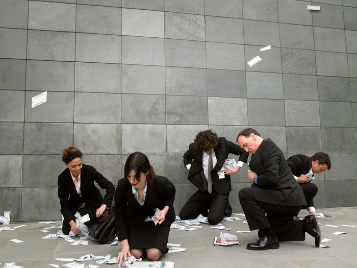 Five businesspeople bending down to pick up money off the floor of an office building