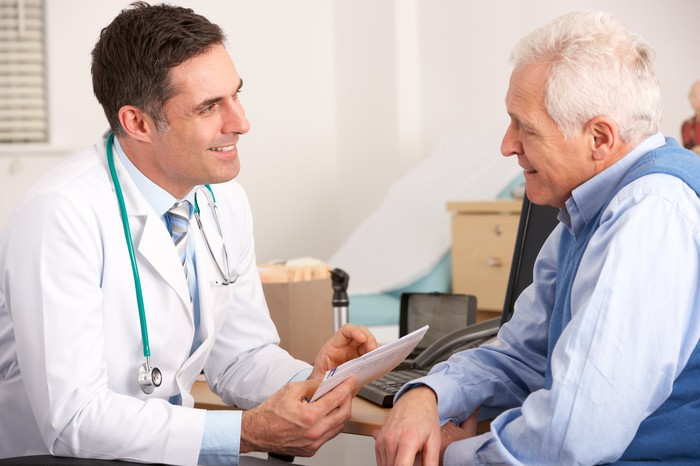 An older male patient talks with a doctor.