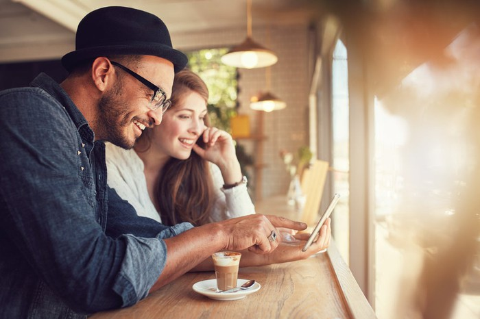 Couple using a mobile device in a coffee shop