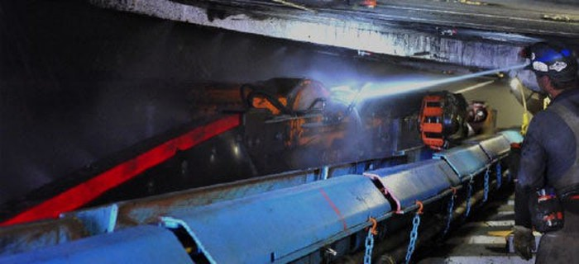 worker inspecting underground coal mining equipment