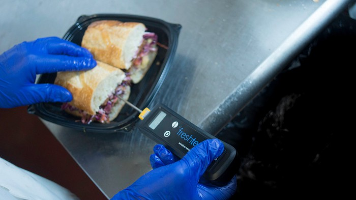 A restaurant worker wearing blue vinyl gloves inserts a Fresh Temp connected thermometer into a sandwich.