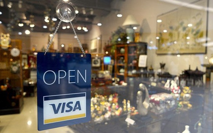 "Sign hanging in store window displaying Visa card and saying ""Open"""