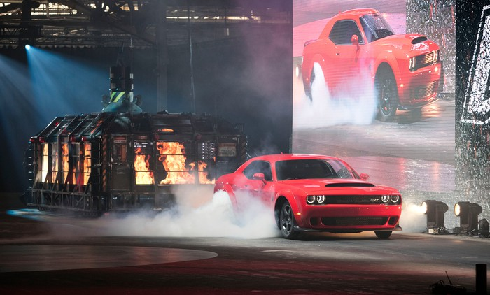 The Dodge Challenger SRT Demon, a red coupe, emerges in a cloud of tire smoke.