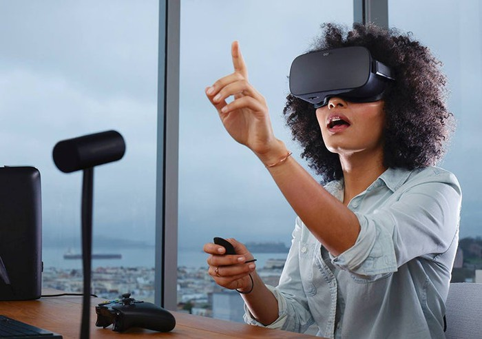 A woman sits at a desk wearing an Oculus virtual reality headset, pointing up at something she must be seeing inside the virtual world.