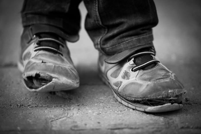 A black and white photo of a child's worn down shoes.
