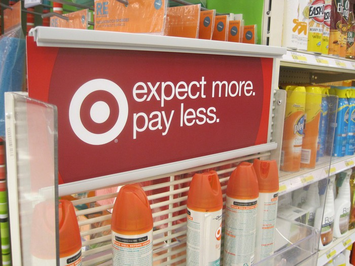 """The Target slogan  """"Expect More. Pay Less is shown on a store shelf."""